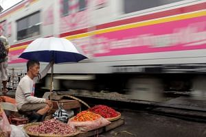 An Indonesian vendor waits for customer as he sells onions and chilies at a market in Bogor, Indonesia, Dec 17, 2015.
