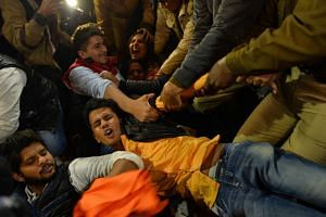 Indian demonstrators shout slogans as they attempt to prevent others from being detained by police officials. They were at a rally in New Delhi on Dec 20, 2015, held to protest the release of a juvenile rapist.