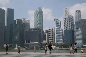 Tourists walking along the path on the waterfront promenade, along Marina Bay Sands as the skyline of Singapore CBD stands in the background.