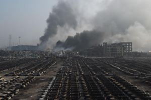 Smoke billowing behind rows of burnt out cars at the site of a series of explosions in Tianjin, northern China on Aug 13, 2015.