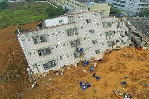 Rescue workers climb up a damaged building on Monday. Some 76 people remain missing under tonnes of earth and wreckage spanning the size of 50 football fields. The landslide on Sunday morning buried 33 buildings in an industrial park in Guangming New