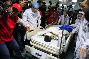 Medical staff pushing landslide victim Tian Zeming on a stretcher after surgery in a Shenzhen hospital.