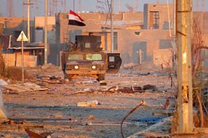 A member of Iraq's counter-terrorism forces monitors his surrounding in a street in Ramadi's Dhubbat neighbourhood.