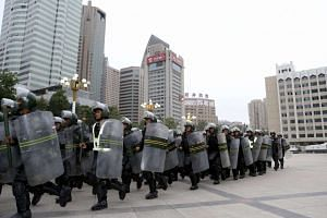 Armed paramilitary policemen run in formation during a gathering to mobilise security operations in Urumqi, Xinjiang.