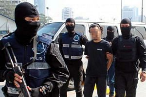 A suspect believed to be a member of the Islamic State in Iraq and Syria (ISIS) being detained by the Malaysian police for allegedly planning a series of terror attacks in the Klang Valley in Kuala Lumpur.