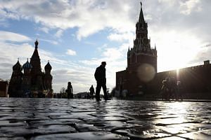 People crossing Red Square, with the Kremlin's Spasskaya Tower (right) and St. Basil's Cathedral in the background.