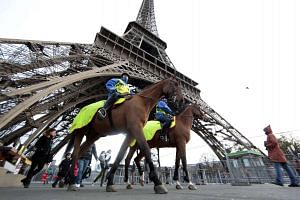 Mounted guards patrol under the Eiffel Tower in Paris on Nov 28, 2015.