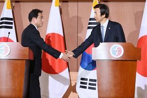 Japanese Foreign Minister Fumio Kishida (left), and South Korean counterpart Yun Byung-Se (right) shake hands during a joint press conference after their meeting in South Korea on Dec 28.