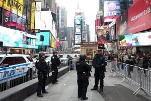 Police officers on patrol on Sunday in New York City's Times Square (above), where up to one million party-goers are expected to ring in the new year. Thousands of officers will be on patrol there, and a new unit of 500 police officers trained to wor