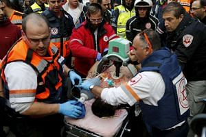 Medics evacuate a wounded person from the scene of a shooting incident in Tel Aviv on Jan 1, 2016.