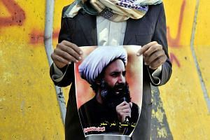 A file picture dated Oct 18, 2014 showing a supporter of the Yemeni Shi'ite Houthi movement holding a banner depicting Saudi Shi'ite leader Nimr Baqir al-Nimr during a protest. Al-Nimr was among 47 people executed on Jan 2, 2016.