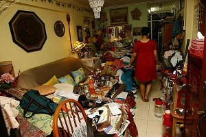 Above: Ms Julia seen here in 2010 in her two-room HDB flat which was filled with old newspapers, plastic bags, boxes and clothes. Left: Because there was no space for Ms Julia's mum, Madam Mainam Mahmud, to rest well at night, the elderly woman had t