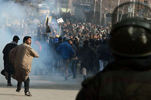 Kashmiri Shiite protesters shout slogans as they run from teargas smoke during a demonstration in Srinagar on Jan 3, 2016, against the execution of prominent Shiite Muslim cleric Nimr al-Nimr by Saudi authorities.