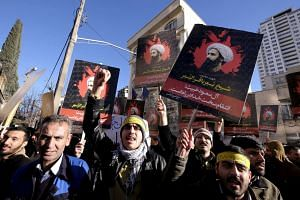 Iranian protesters holding pictures of Shi'ite cleric Sheikh Nimr al-Nimr during a demonstration  outside the Saudi Arabian Embassy in Teheran on Jan, 3, 2016.