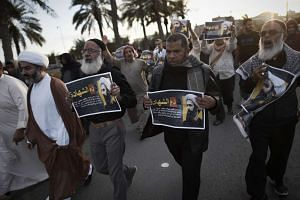 Bahraini protestors hold posters of executed Shiite Muslim cleric Nimr al-Nimr during a protest in Manama on Jan 3, 2016.