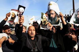 Iraqis holding pictures of Shi'ite cleric Nimr al-Nimr, who was execurted in Saudi Arabia, during a protest in Baghdad on Jan 4.