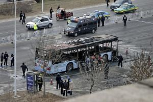 Firefighters and policemen working next to a  bus that was set on fire on a street in Ningxia, China, on Jan 5, 2016.