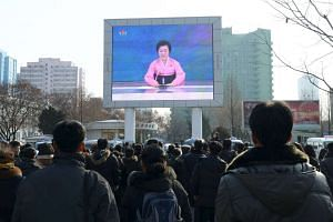 People watch a huge screen broadcasting the government's announcement in Pyongyang, North Korea.