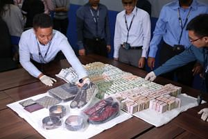 (Above) Police recovered about $433,000 in cash and several luxury goods from a room in MBS, where the two Vietnamese men were staying. They allegedly broke into a fruit wholesale shop in Pasir Panjang and stole the money.