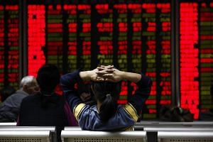 An investor views stock market data on an electronic board at a securities brokerage house in Beijing.