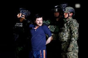 "Soldiers escort drug lord Joaquin ""El Chapo"" Guzman during a presentation to the media in Mexico City."