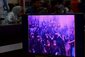 Reporters watch a video recording showing East Indonesian Mujahidin, led by Santoso, at police headquarters in Palu, Indonesia Central Sulawesi province, Dec 31, 2015.