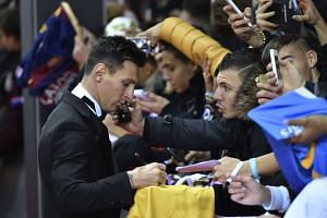FC Barcelona and Argentina's forward Lionel Messi (left) sign autographs on the red carpet as he arrives for the 2015 FIFA Ballon d'Or award ceremony at the Kongresshaus in Zurich on  Monday.