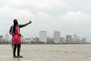 A couple taking a selfie on Marine Drive promenade in Mumbai. It is one of 16 places identified by police in the Indian city as dangerous selfie spots after a man drowned as he tried to save a girl and her two friends who had fallen into the sea whil