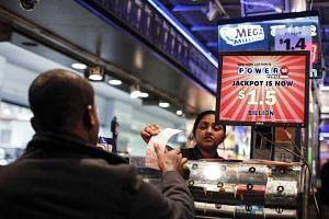 A man buys a Powerball lottery ticket at a newsstand in New York City on Tuesday.