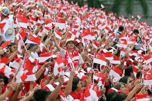Spectators waving Singapore flags during the Golden Jubilee National Day Parade at the Padang on Aug 9, 2015.