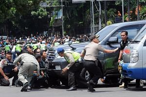Indonesian police officers taking cover behind a vehicle during an exchange of gunfire with militants, after a series of blasts in downtown Jakarta yesterday.