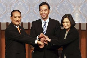 (From left) Taiwan's presidential candidates James Soong, Eric Chu and Tsai Ing-wen joining hands at the start of their first televised debate in Taipei on Dec 27, 2015.