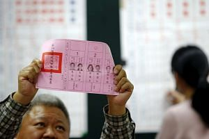 An election official shows a ballot with vote for DPP presidential candidate Tsai Ing-wen.