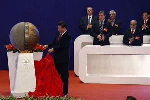 Chinese President Xi Jinping (left) unveils a sculpture during the opening ceremony of the AIIB on Jan 16, 2016.