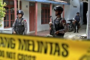 Armed Indonesian police standing guard in front of a house during a raid.