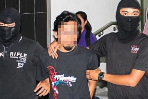 The Malaysian man being escorted by security officials after he was detained.