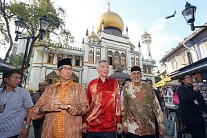 Prime Minister Lee Hsien Loong and Dr Yaacob Ibrahim joining Mr Mohamed Patail (right, in photo at left) at Sultan Mosque yesterday for an event to mark the completion of its upgrading. New features for the mosque, gazetted a national monument in 197