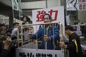 A protester wearing a mask of missing bookshop co-owner Lee Bo stands behind bars during a protest in Hong Kong last Sunday. Booksellers have recently landed in hot water for peddling books that claim to give an insider's view of the public and priva