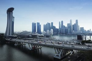 Traffic flows in front of the skyline in Singapore.