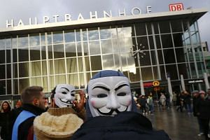 People wear Guy Fawkes masks as they gather outside the main railway station in Cologne, Germany, on Saturday, Jan 16, 2016, where the vast majority of dozens of New Year Eve assaults on women took place.