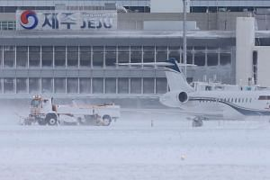 A snowplough clears runways at Jeju International Airport on the southern resort island of Jeju in South Korea on Jan 24, 2016.