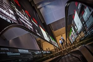 Pedestrians exit an escalator that runs past an electronic screen and ticker board that indicates stock figures at the Singapore Exchange Ltd headquarters.