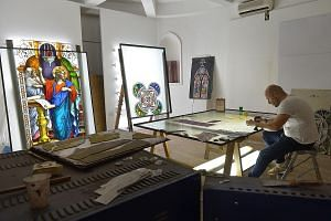 Artisan Ernesto Raducci, 40, at work in Singapore on Friday, carefully beautifying the stained glass that will be installed in the new extension. When Novena Church opens its doors early next year, worshippers can look forward to a new heritage centr
