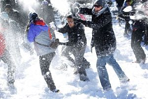 People participate in the massive snowball fight at Dupont Circle in Washington, DC on Sunday.