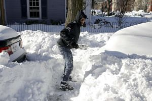 A man digs a car out of the snow after a major winter storm swept over Washington on Sunday,