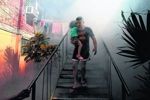 A man carrying his son away from his home as health workers fumigated the Altos del Cerro neighbourhood in El Salvador last week, as part of preventive measures against the Zika virus and other mosquito-borne diseases.