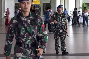 Indonesian soldiers stand guard at Ngurah Rai international airport in Bali, Indonesia, on Jan 20, 2016.