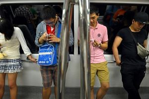 Passengers using their mobile phones on board a train.