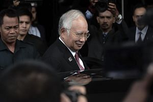 Malaysian Prime Minister Najib Razak (centre) leaving after attending a Parliament session in Kuala Lumpur yesterday. Attorney-General Apandi Ali has cleared Mr Najib of any criminal wrongdoing involving US$681 million donated by the Saudi royal fami