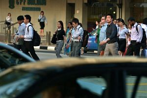 Office workers cross a road in the Central Business District (CBD) of Singapore.